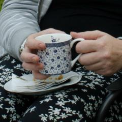 Patient's hands holding cup of tea